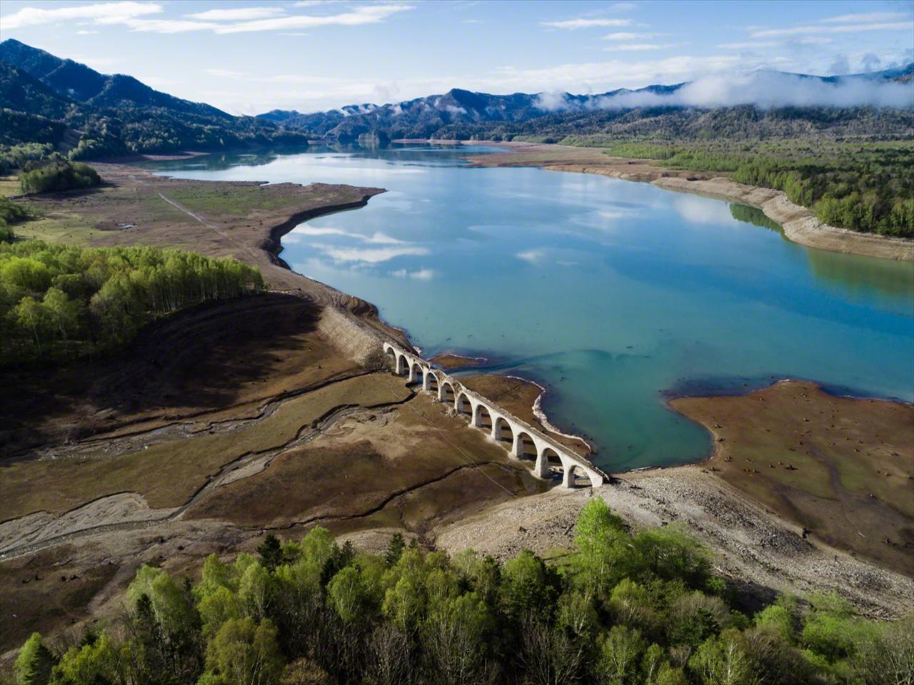 En mayo el paisaje se cubre de verde. La nieve derretida fluye hasta el lago y la superficie del agua se acerca a la base del puente.