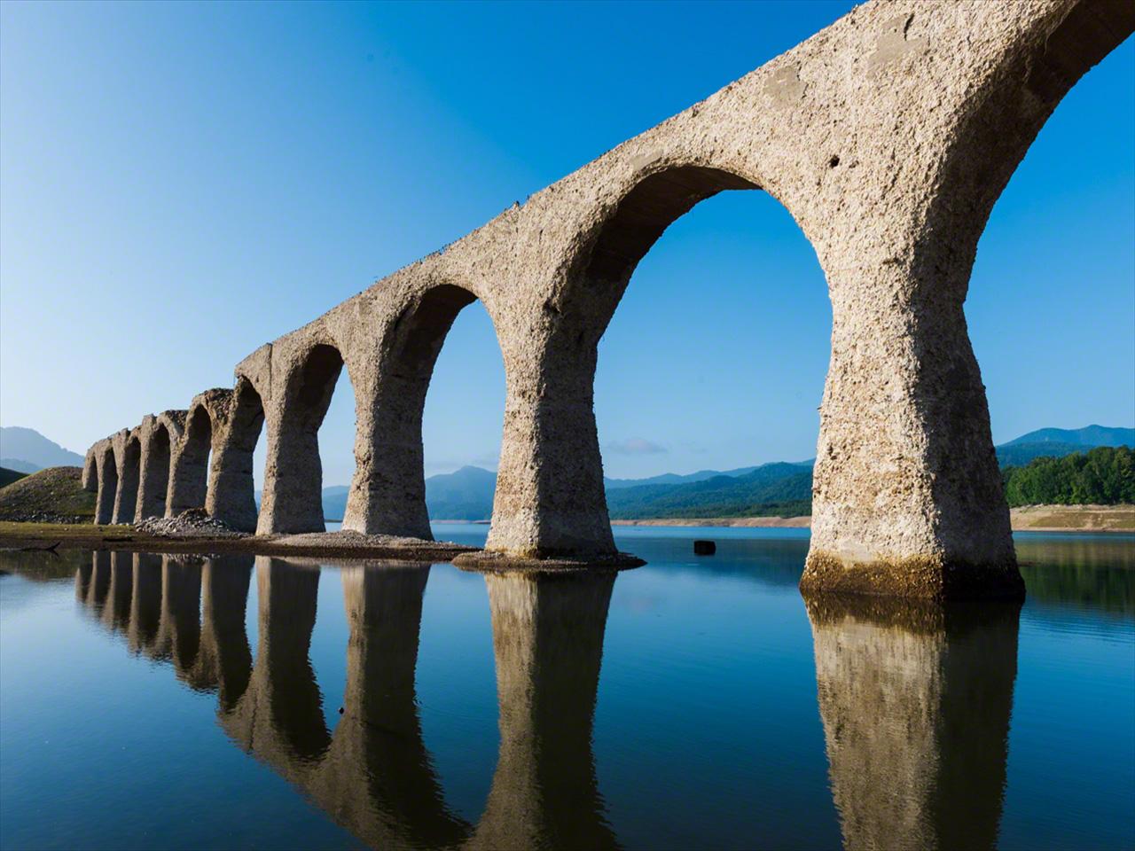 """Julio. El puente en arco se refleja perfectamente en la superficie del lago los días sin viento, por lo que también recibe el nombre de """"puente de las gafas""""."""