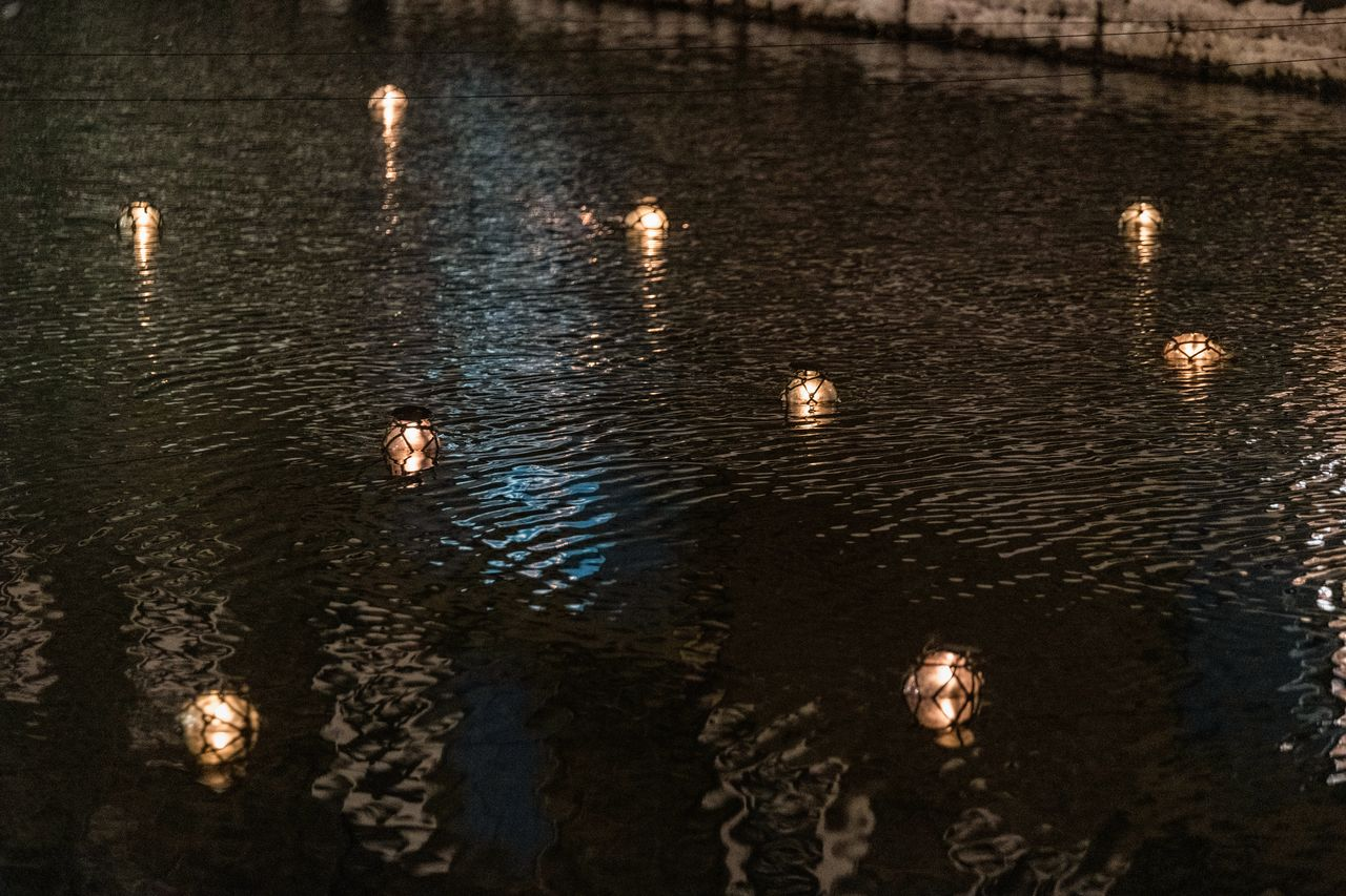 Les bougeoirs flottants en verre illuminent le canal.