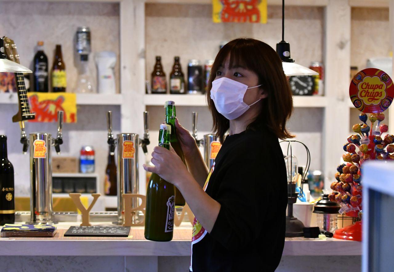 Katô Emi en train de servir des clients à son bar, le Yellow Beer Works.