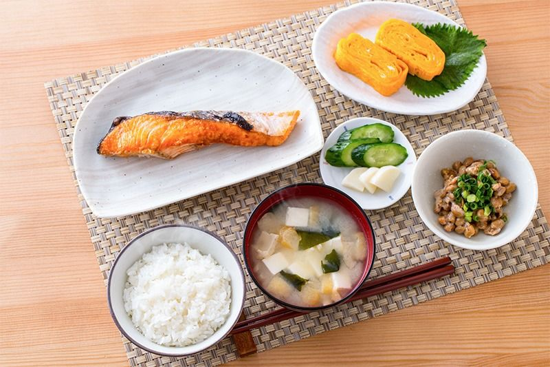 典型的日式早餐(從右下角順時針依次為:香蔥納豆、豆腐海帶味噌湯、白飯、烤鮭魚、泡菜、蛋捲)