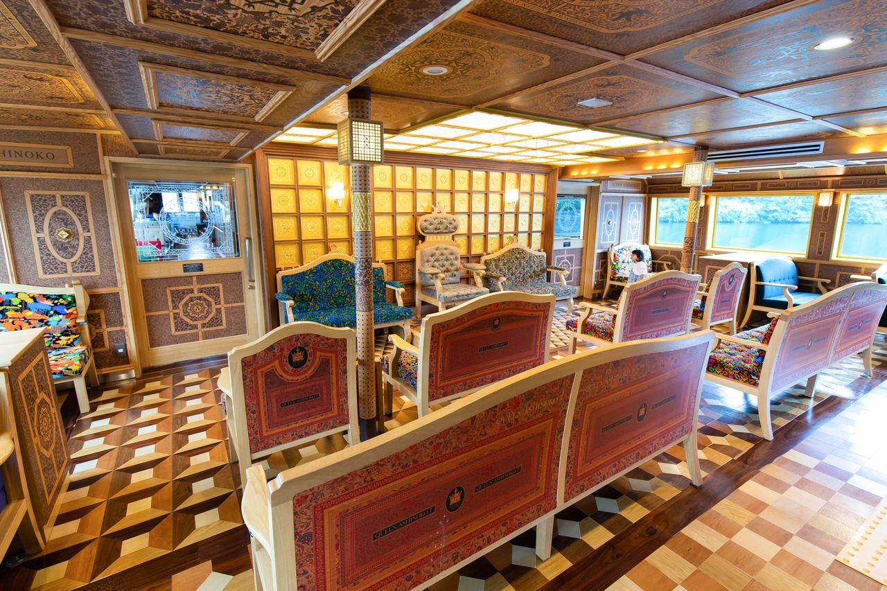 ゴージャスな特別船室。高級感あふれるソファはもちろん、箱根寄せ木細工風の床やさまざまな模様をあしらった木目調の天井まで、一切手抜きのない水戸岡デザインは圧巻