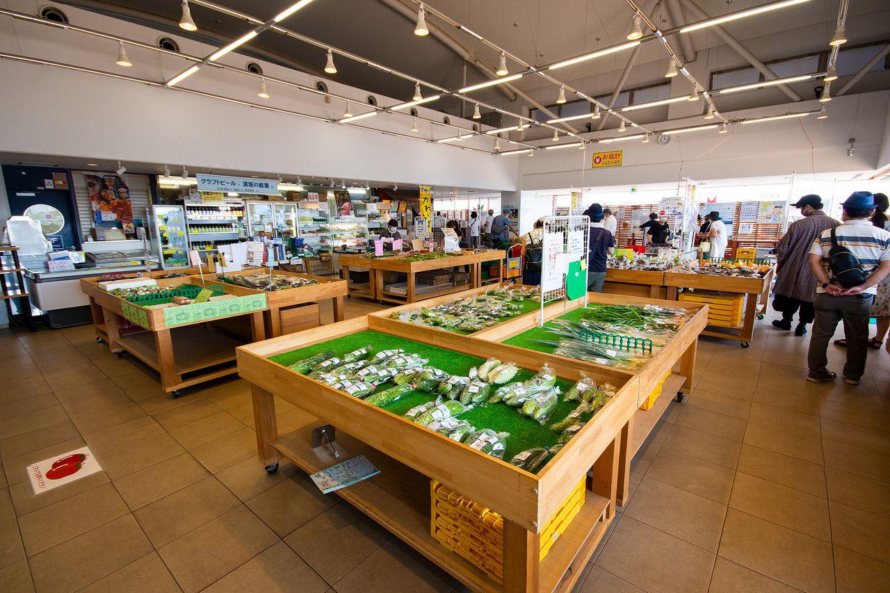 朝採れの野菜が平台に並ぶ2階のやさい館。果物の生ジュースや地ビールが飲めるコーナーも