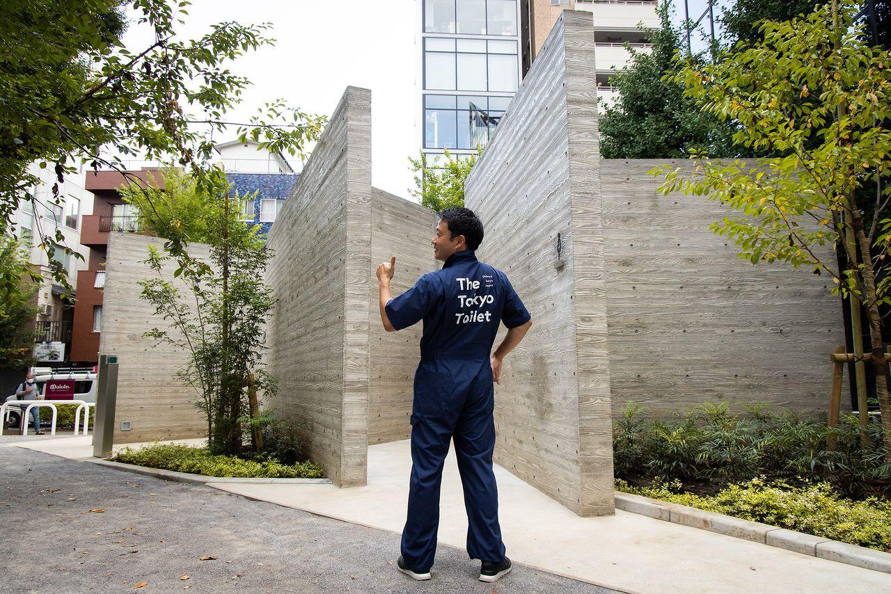 恵比寿公園トイレの前で、清掃員のユニホーム姿でポーズを取る笹川理事。「かっこいいだけでなく、伸縮性があって動きやすい。清掃員の方にもプライドを持って仕事してもらえれば」と言う