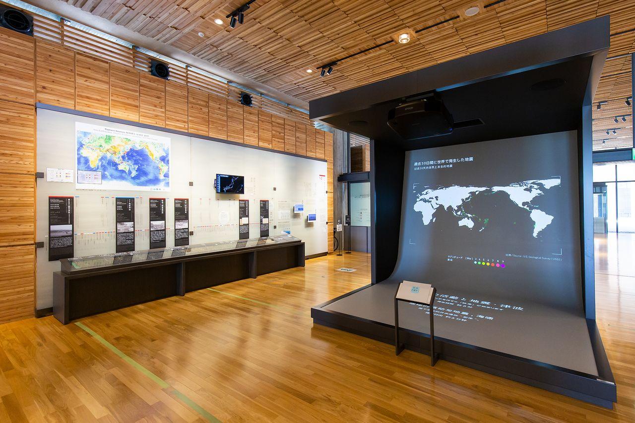 左は三陸地方の津波の年表と地層の展示。右のスクリーンでは、世界中で最近発生した地震の状況を把握できる