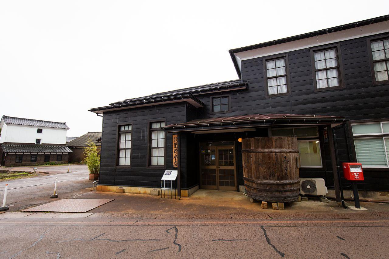 味噌やしょうゆを製造する「星野本店」前には大きな木桶(おけ)が置いてある。左奥に見える蔵(登録有形文化財)は、珍しい3階建て
