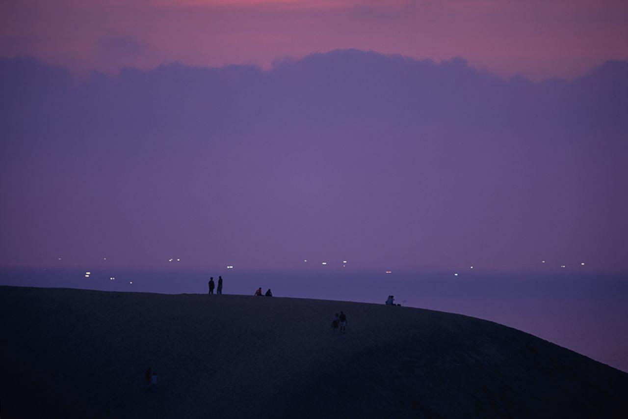 夕暮れに浮かび上がる砂丘のシルエットのJ向こうにいさり火が見える 写真提供:鳥取県