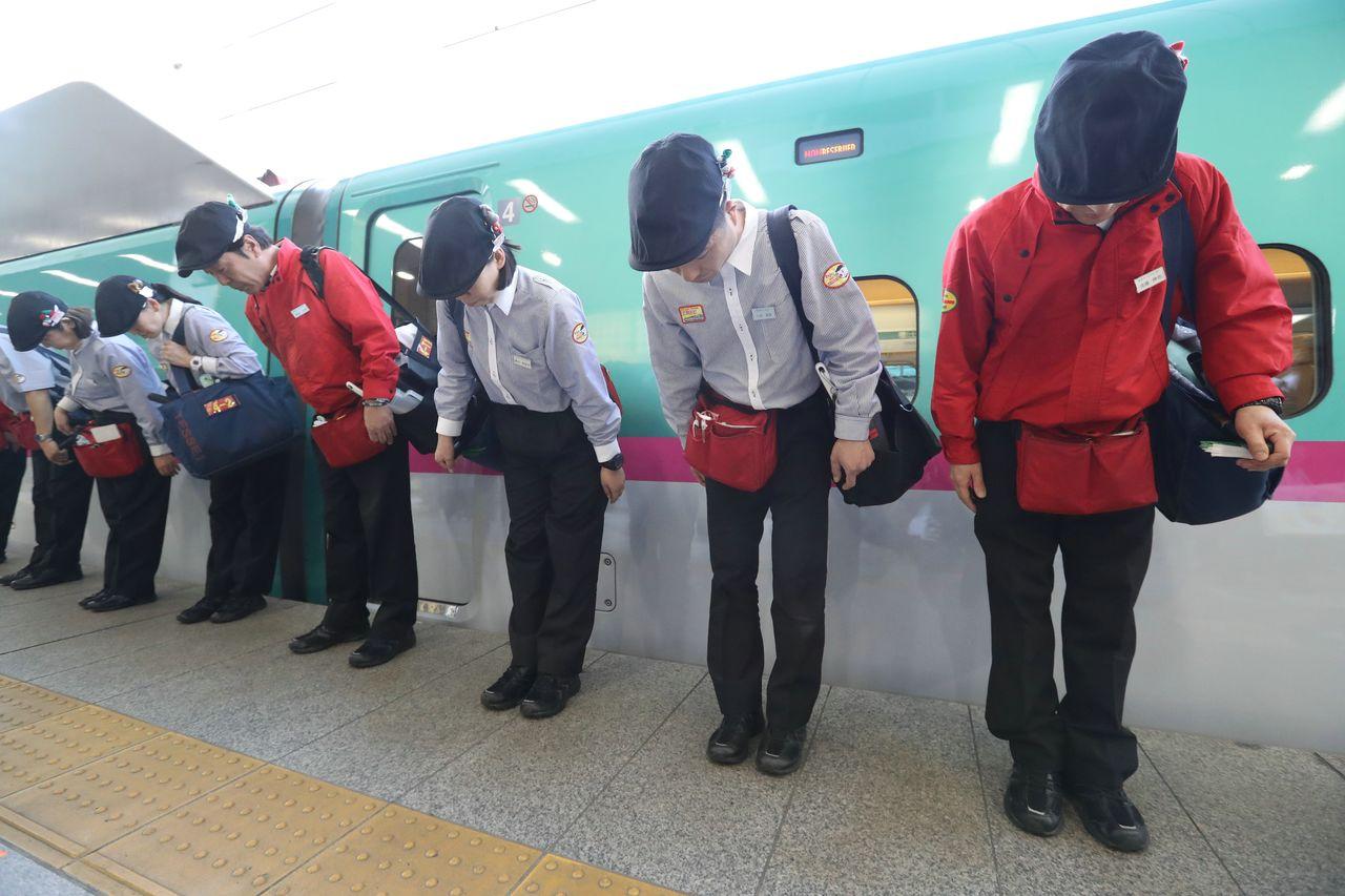 新幹線の車内清掃を終え、ホームで一礼する担当者=JR東京駅(時事)