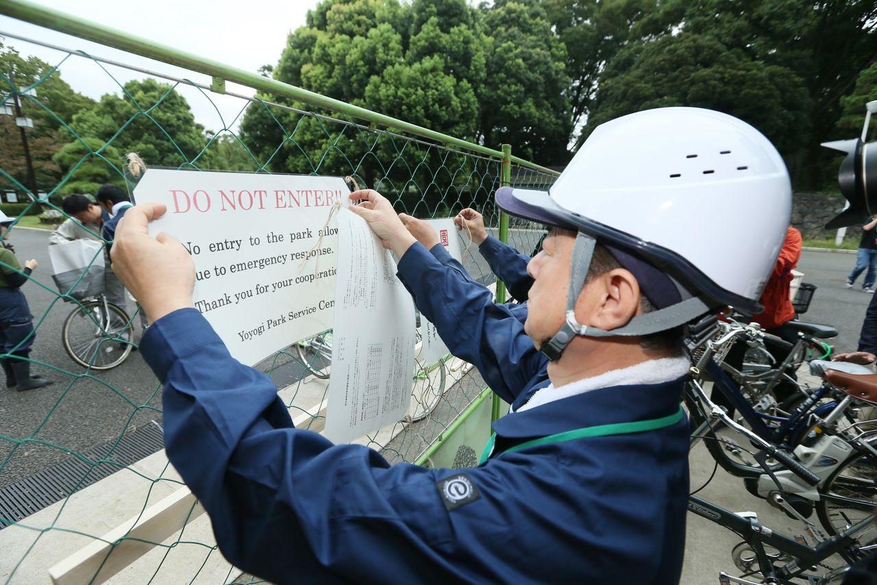 採集した蚊からデング熱ウイルスが検出されたことを受け、代々木公園閉鎖の張り紙をする公園関係者=2014年9月4日、東京都渋谷区(時事)