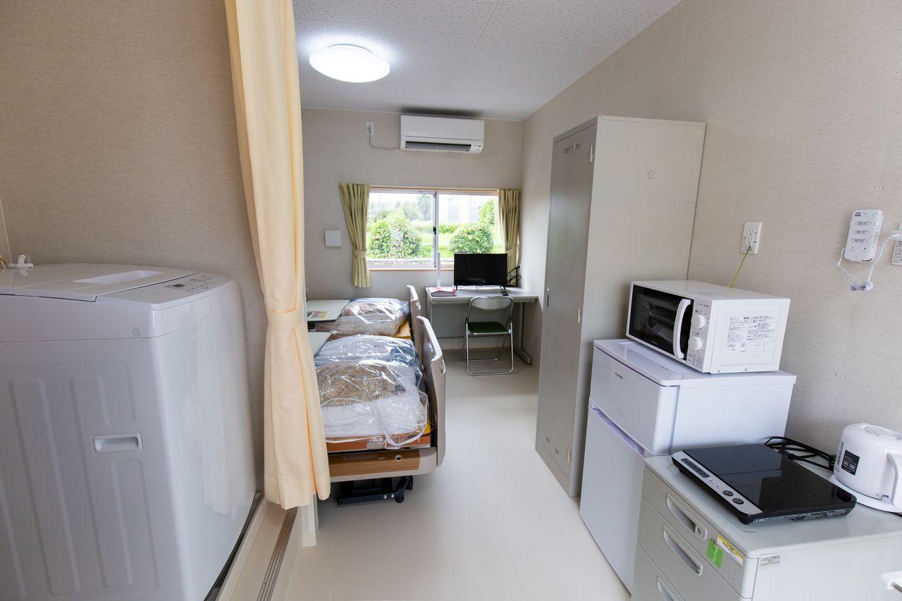 家族用ツーベッドの部屋。手前左に洗濯機が置かれている
