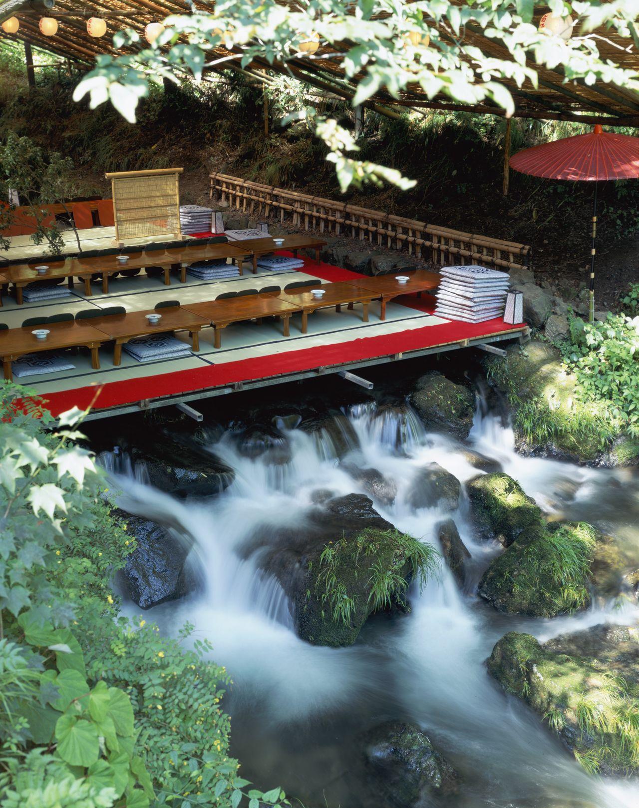 貴船川に設(しつら)えられた納涼床。涼しげな川の流れを目で楽しみながら、京料理を味わう(京都市左京区=2009年撮影、時事)