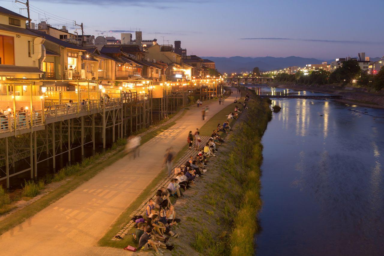 鴨川の納涼床と川岸でくつろぐ人々。5月から9月まで、約90軒の料理屋が軒を連ねる(京都市中京区、PIXTA)