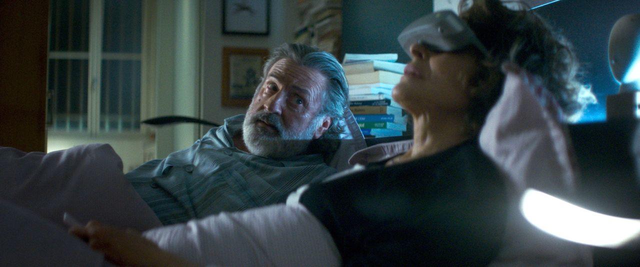 夫ヴィクトル(ダニエル・オートゥイユ)には目もくれず、VRゴーグルを装着し眠りにつこうとする妻マリアンヌ(ファニー・アルダン) ©2019 - LES FILMS DU KIOSQUE - PATHÉ FILMS - ORANGE STUDIO - FRANCE 2 CINÉMA - HUGAR PROD – FILS – UMEDIA