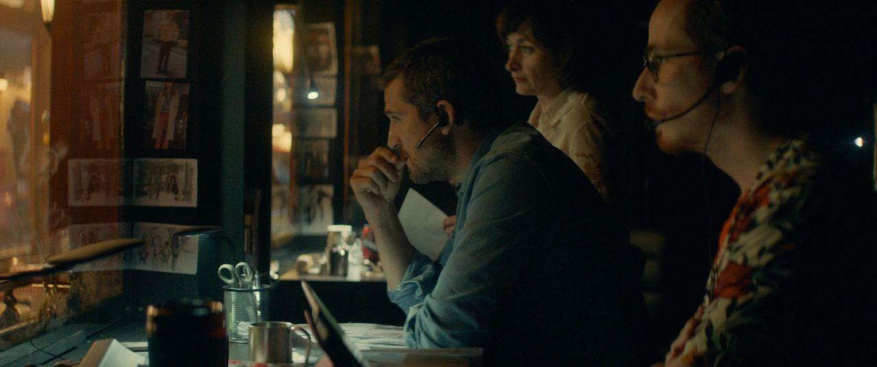 「時間旅行」を指揮するアントワーヌ(ギョーム・カネ)は、マジックミラーの背後に控え、イヤホンを仕込んだ役者にインカムで細かく指示を出す ©2019 - LES FILMS DU KIOSQUE - PATHÉ FILMS - ORANGE STUDIO - FRANCE 2 CINÉMA - HUGAR PROD – FILS – UMEDIA