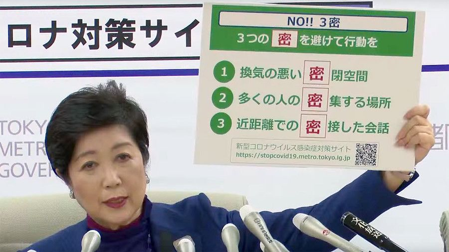 Tokyo Governor Koike Yuriko explaining the 3 C's with a placard.