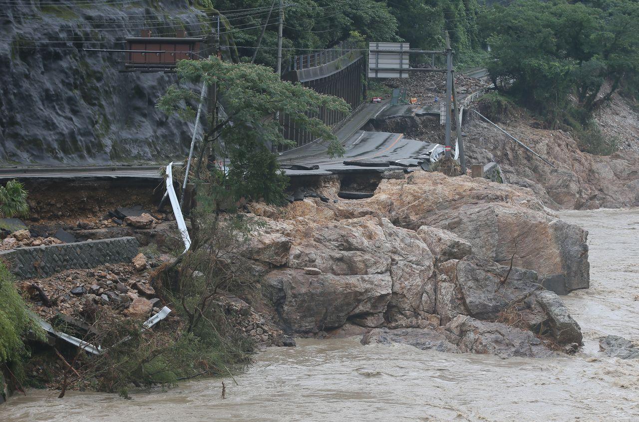 大雨で崩落した国道。手前は球磨川=2020年7月6日午前、熊本県芦北町と球磨村の境(時事)