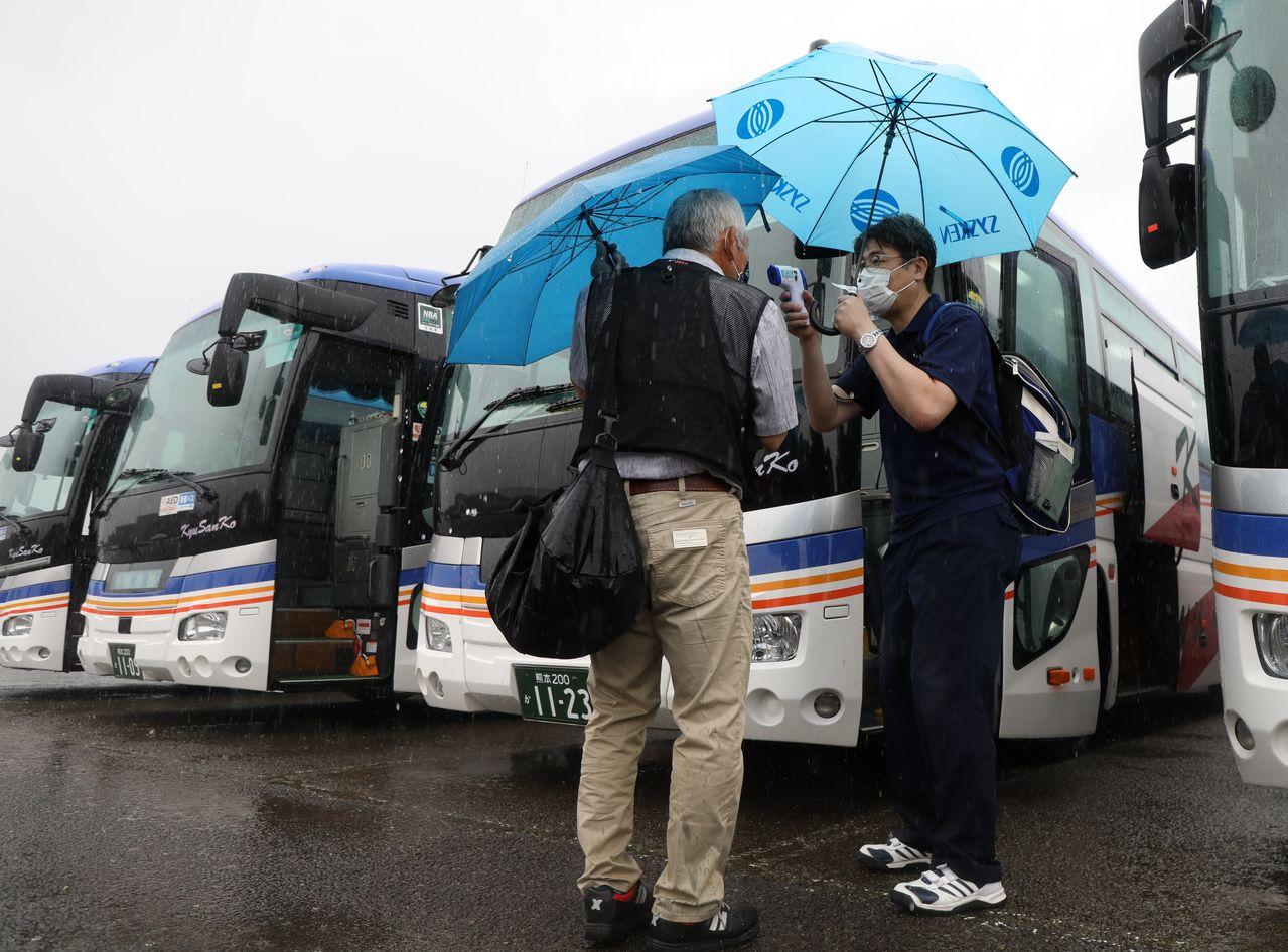 熊本市への広域避難のためバスに乗る前に、検温を受ける人吉市の住民=2020年9月6日、熊本県人吉市(時事)