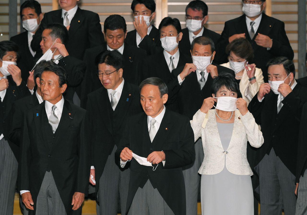 皇居での首相親任式と閣僚認証式後の記念撮影を終え、マスクをつけながら車を待つ菅義偉首相(手前中央)と閣僚ら=2020年9月16日、皇居(時事)