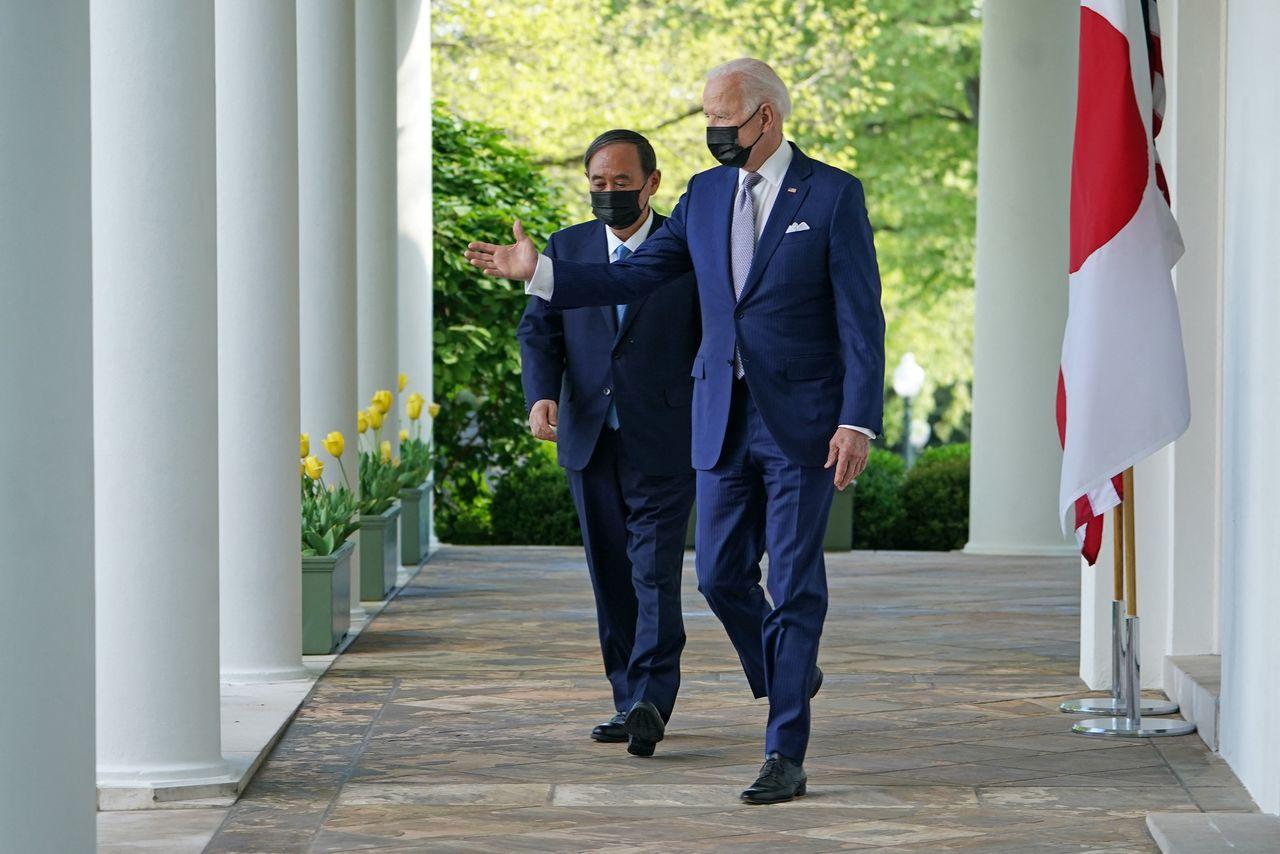 ホワイトハウスで、マスクをして記者会見場へ向かう菅義偉首相(左)とバイデン米大統領(米ワシントン)=2021年4月16日(AFP=時事)