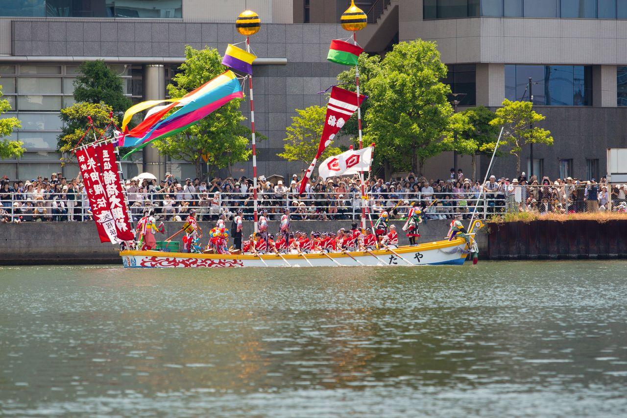 Зрители собрались на берегу реки возле моста Кунибики