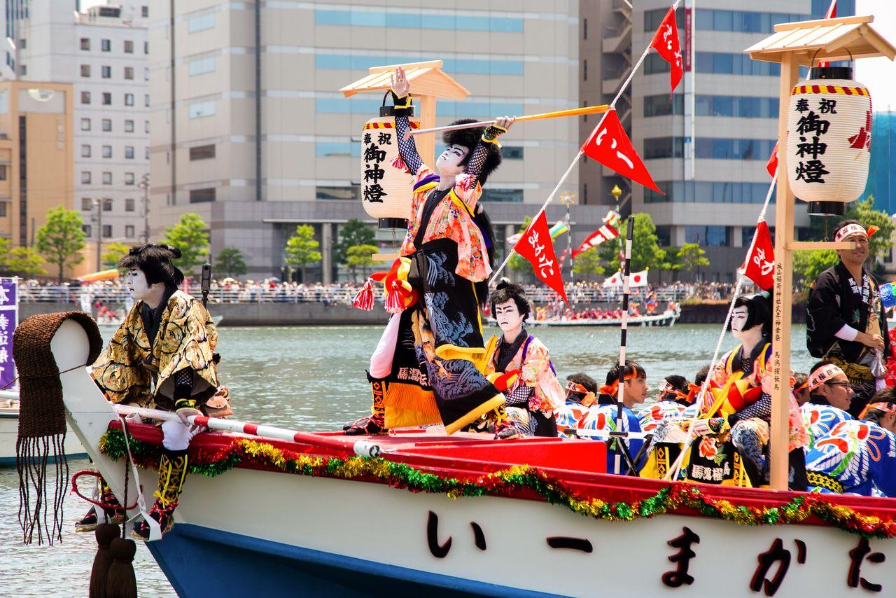 Кэнгай из Маката с гордостью дают представление на лодке с надписью «Первая»