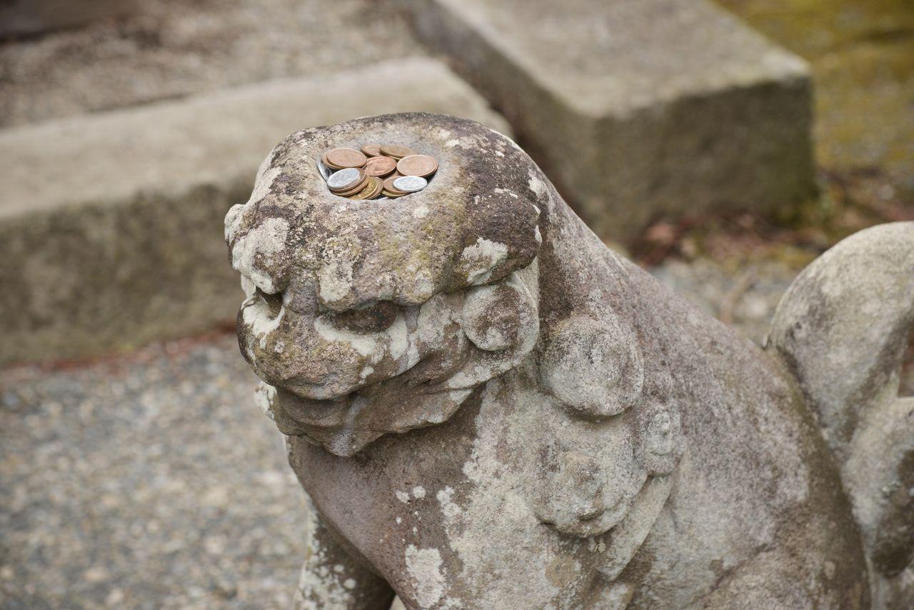 Каппа комаину стоит в стороне у ворот храма