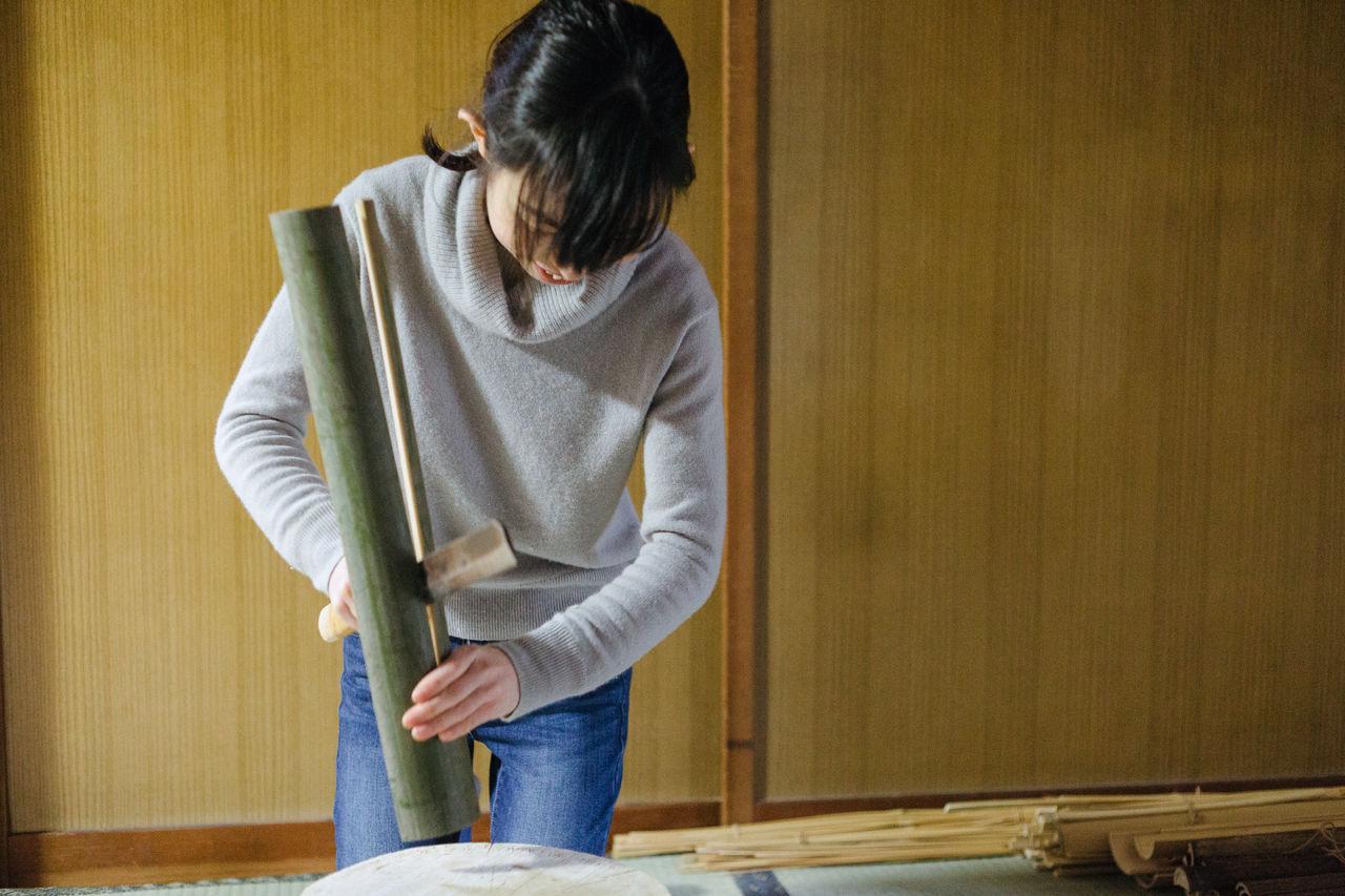 Огура использует нож с широким лезвием, чтобы разрезать кусок бамбука