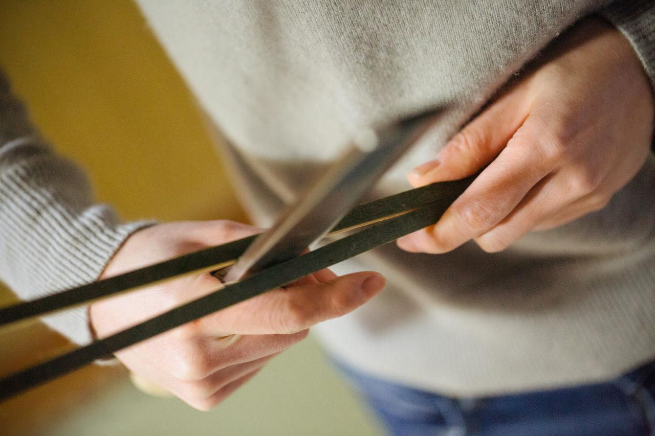 Огура использует нож с широким лезвием, чтобы разрезать бамбук на мелкие полоски