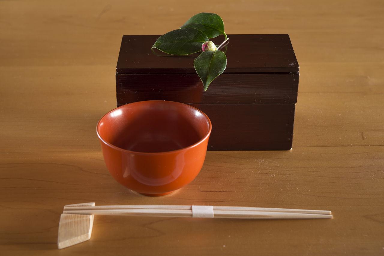 Изысканный японский завтрак-натюрморт: палочки для еды, лакированная чаша и лакированная коробочка для бэнто, украшенная веточкой камелии