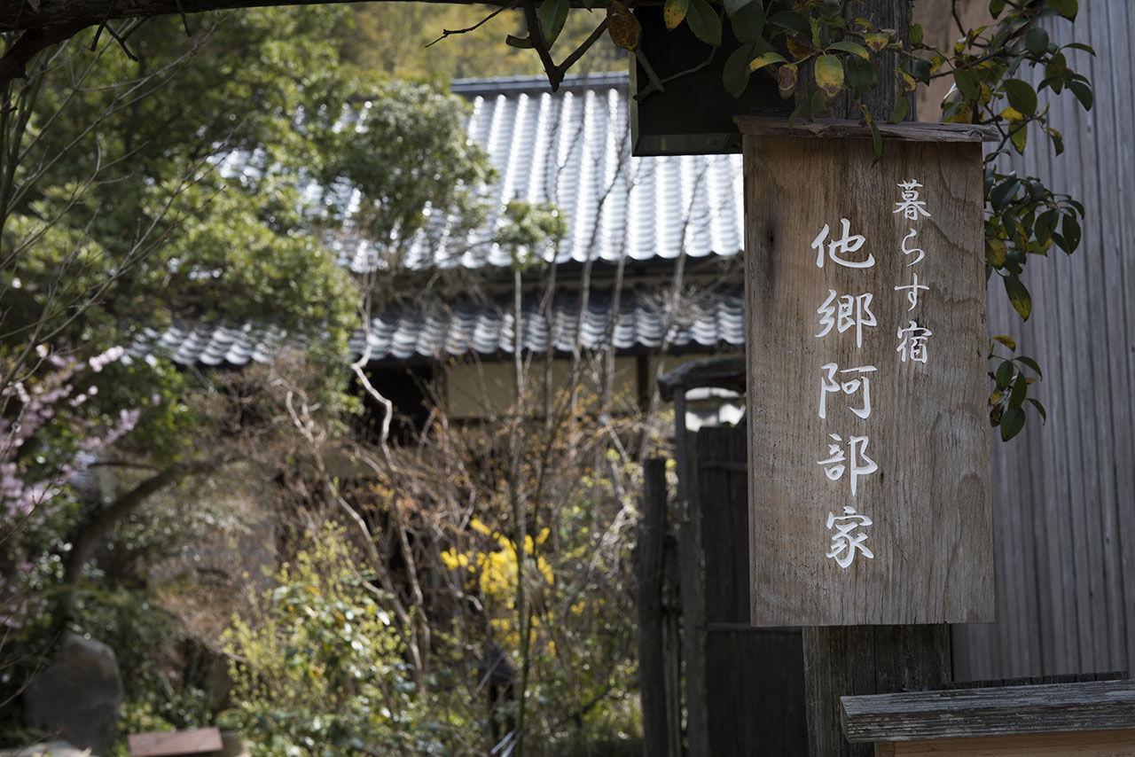 Вывеска в деревенском стиле идентифицирует «Такё Абэкэ» как «курасу ядо», или «домашнюю гостиницу»