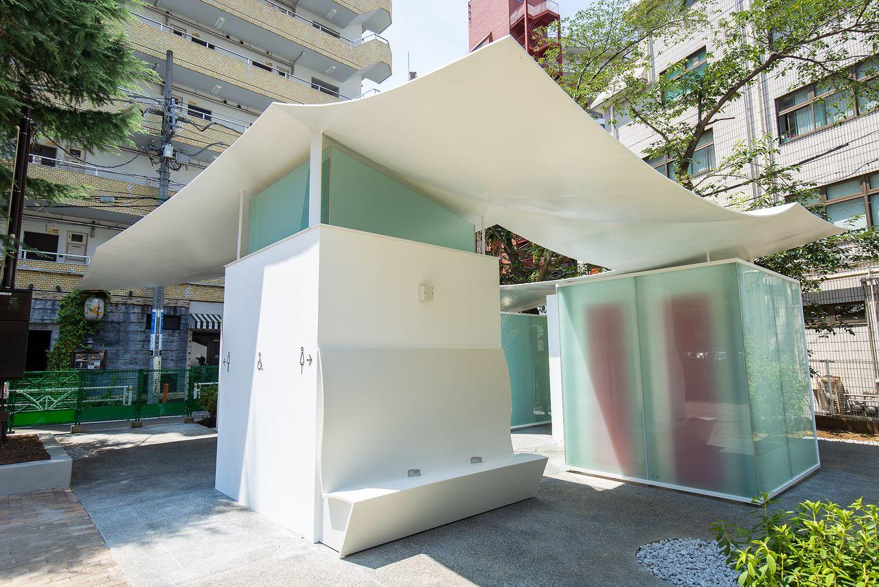 Три туалета соединены плавно изогнутой крышей, на стене устроена скамейка для отдыха