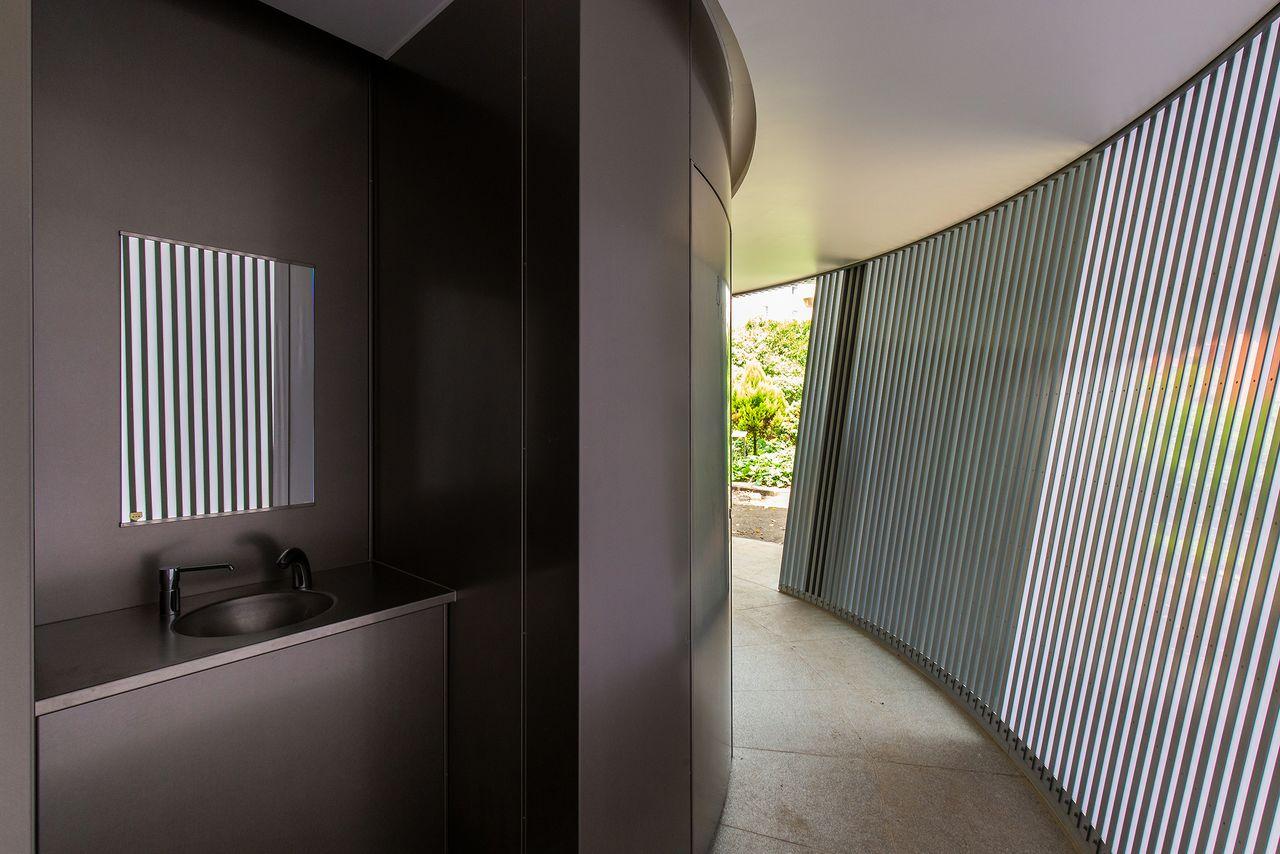 Освещённый проход с решетчатой внешней стеной; за пределами туалетной комнаты находится простая в использовании зона для мытья рук