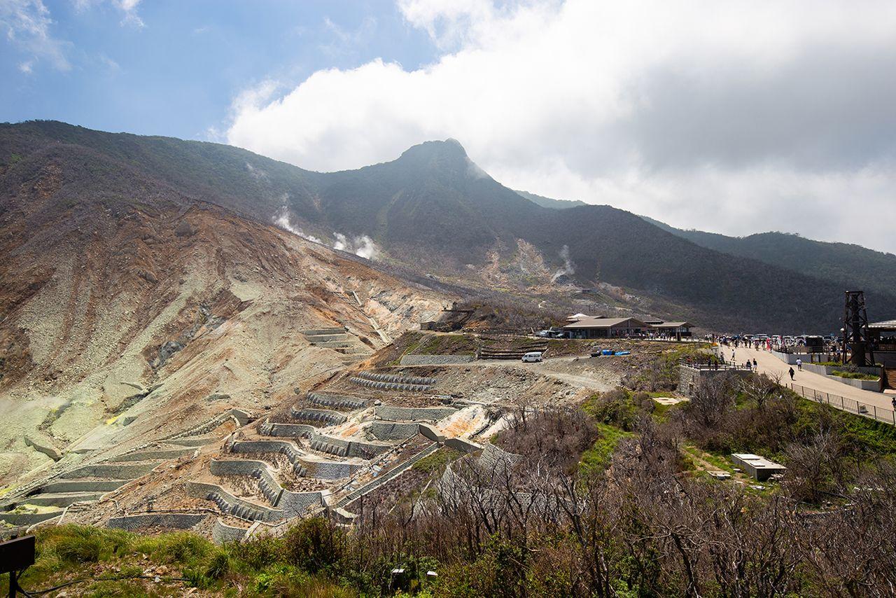 Овакудани и его паровые гейзеры на фоне 1409-метровой горы Каммуригатакэ. Овакусава на переднем плане слева подвержена оползням, её пересекают укрепляющие конструкции