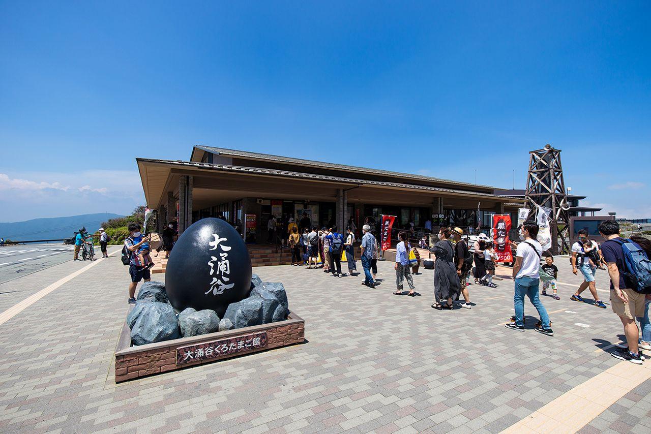 Покупатели в «Куротамаго-кан», крупнейшем сувенирном магазине Овакудани, в очереди за «чёрными яйцами» куротамаго. На территории также есть кафе