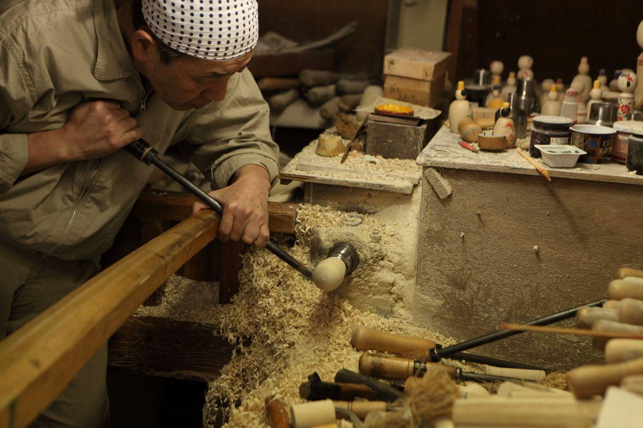 Мастер за изготовлением кокэси в мастерской «Сакураи кокэси». Здесь посетители могут попробовать сами раскрасить свою куклу
