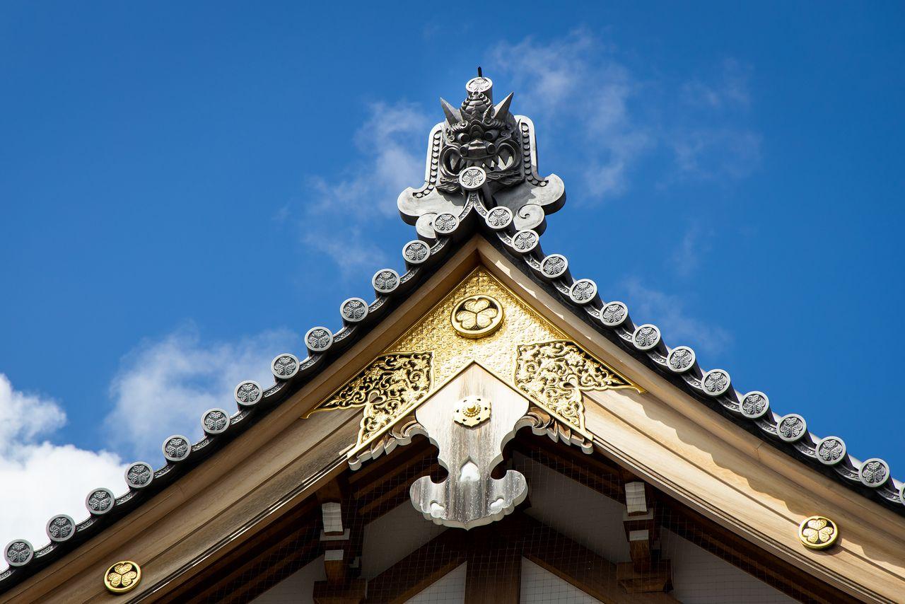 Герб семьи Токугава с тремя листьями мальвы на украшениях крыши под черепицей онигавара с лицом демона на крыше Анкокудэн