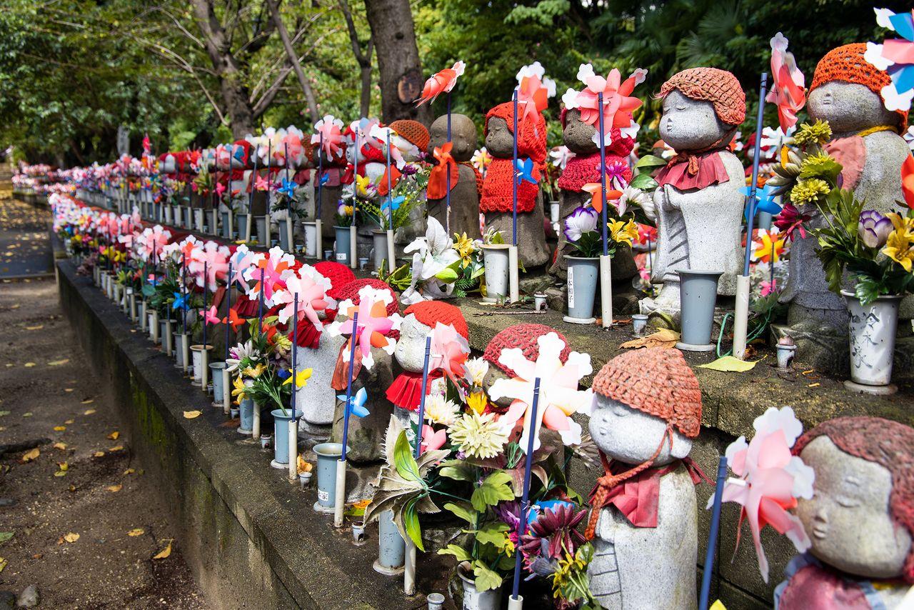 Вертушки и подношения в виде цветов и игрушек украшают ряды статуй Дзидзо, призванных оберегать детей