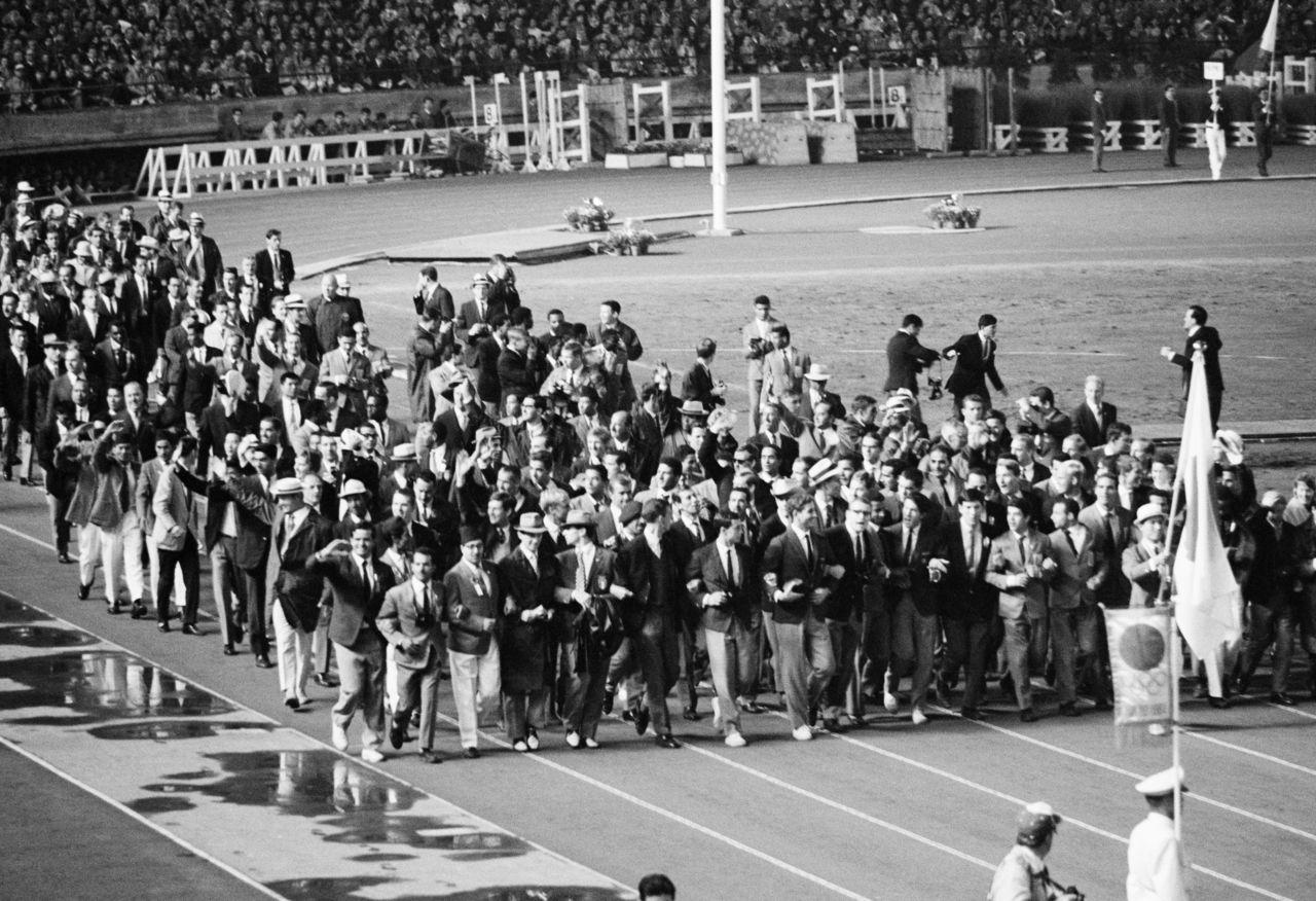На церемонии закрытия Олимпийских игр 1964 года в Токио зарубежные спортсмены смешались и пошли рука об руку