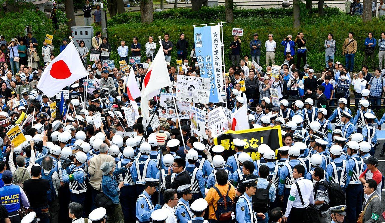 Запланированную в районе Накахара города Кавасаки демонстрацию ненависти участникам пришлось прекратить после того, как их окружили несогласные горожане (июнь 2016 г., © Jiji Press)