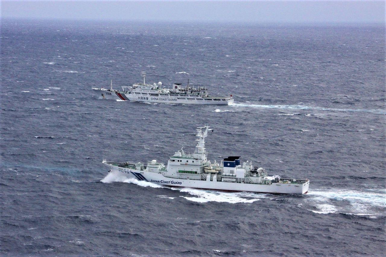 Патрульный катер Управления береговой охраны Японии (на переднем плане), противостоящий судну китайской Береговой охраны (в глубине) в водах у островов Сэнкаку. Напряженность продолжается подолгу (фотография предоставлена Управлением береговой охраны Японии)