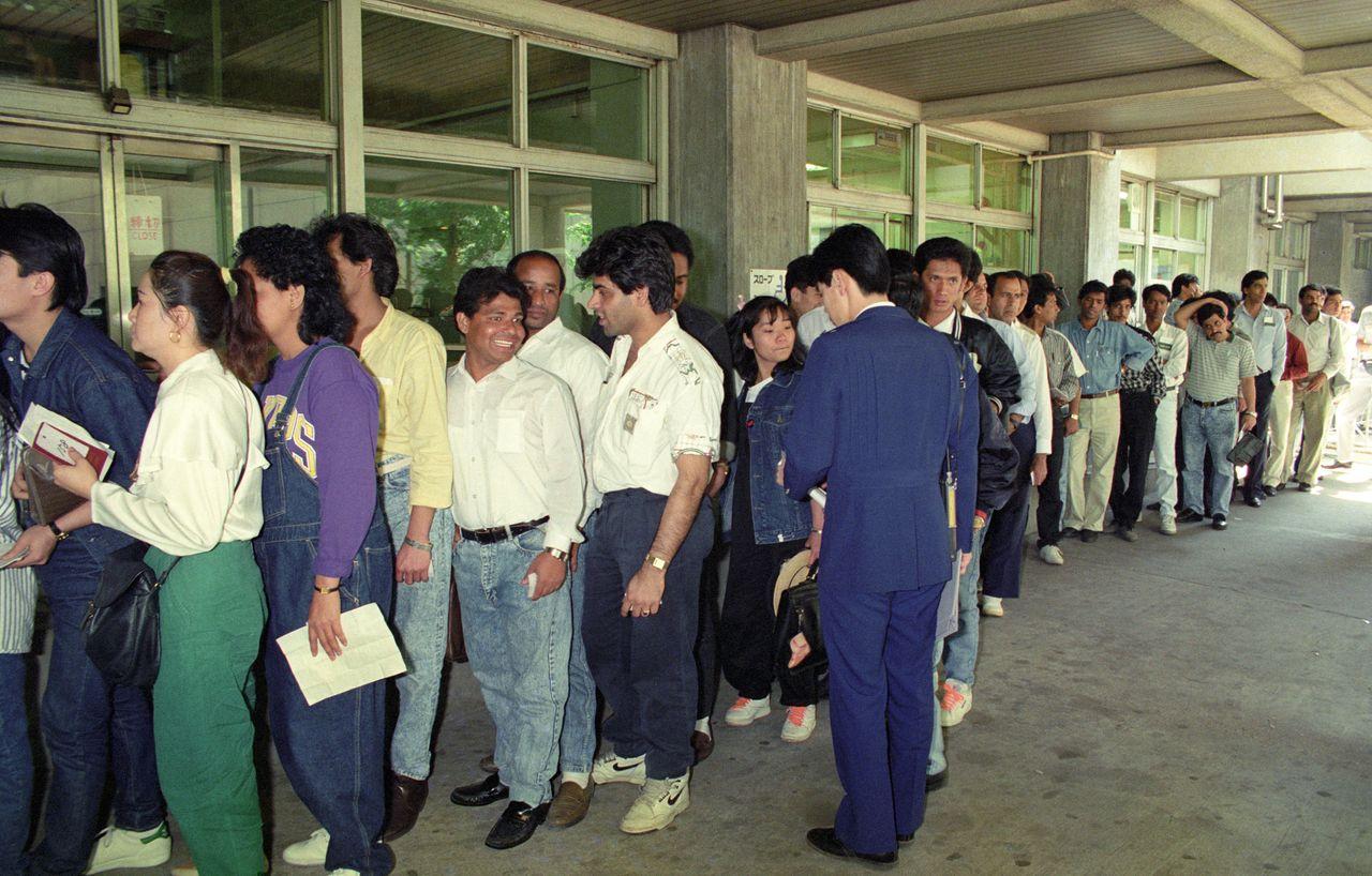 Иностранные рабочие, от которых в связи со вступлением в силу с июня 1990года более строгого Закона об иммиграционном контроле потребовали вернуться на родину, спешат пройти необходимые процедуры (30 мая 1989года, Токио, у здания токийского иммиграционного управления в районе Отэмати. © Jiji Press)