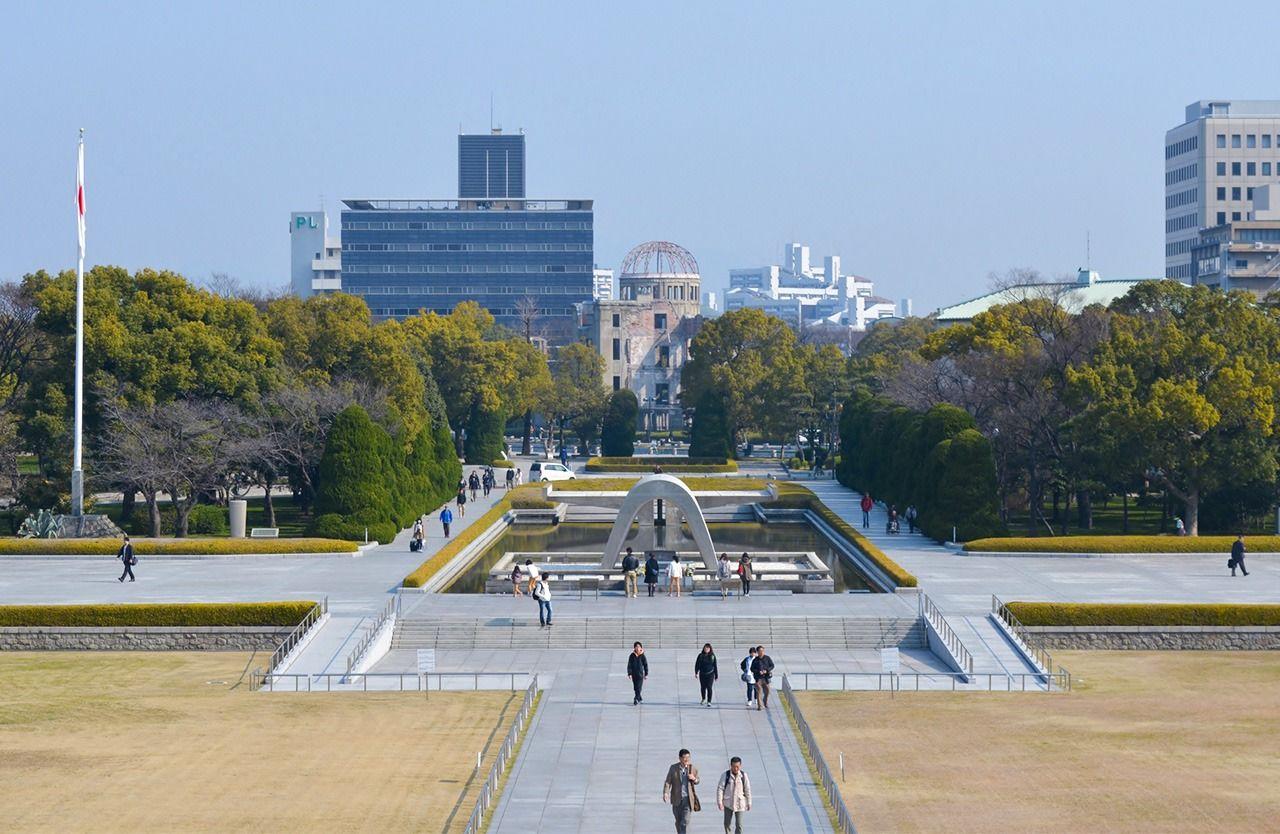 Кенотаф (на переднем плане) и Атомный купол в Мемориальном парке мира в Хиросиме