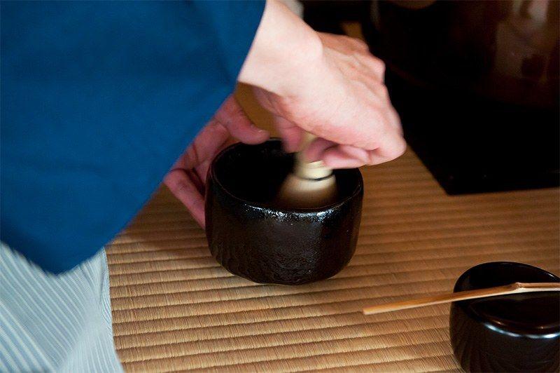 Взбивание чая в чашке во время чайной церемонии (© Pixta)