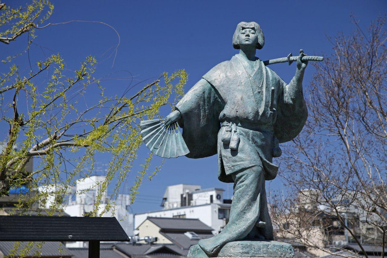 Статуя Идзумо-но Окуни возле моста Сидзё, Четвёртого проспекта Киото, с западной стороны от театра Минамидза. Согласно одной из легенд, путешествовавшая с представлениями Окуни выступала и здесь. Образ танцовщицы взят с изображения на складной ширме-бёбу «Окуни кабукидзу бёбу», внесённой в список Важного культурного достояния (PIXTA)