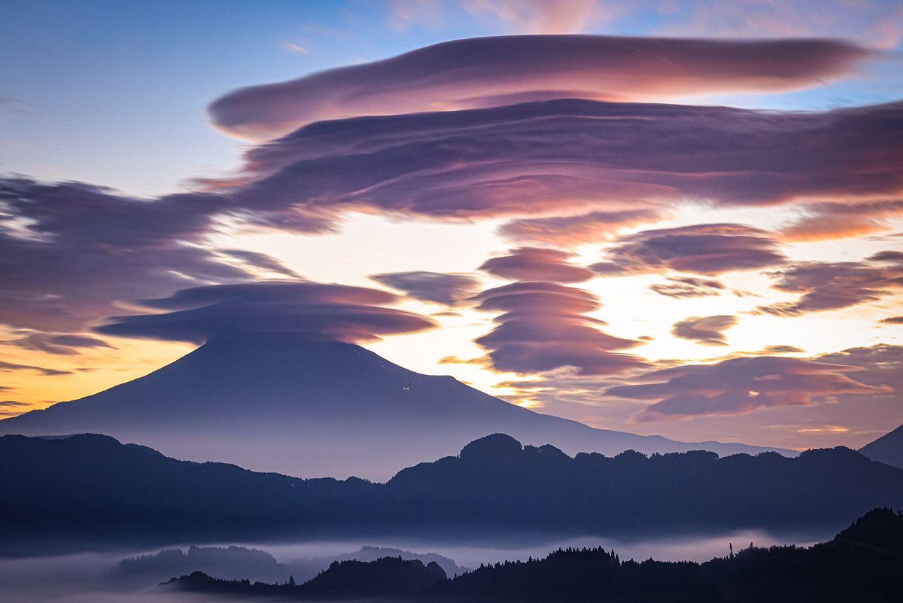 Фотограф опубликовал это фото с комментарием «Она похожа на крепость». Справа – ряд линзовидных облаков