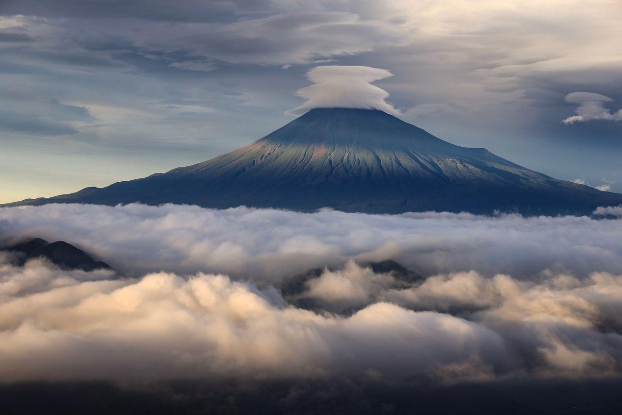 Ярусы линзовидных облаков на вершине горы летом, внизу на переднем плане – море облаков в Симидзу Ёсивара