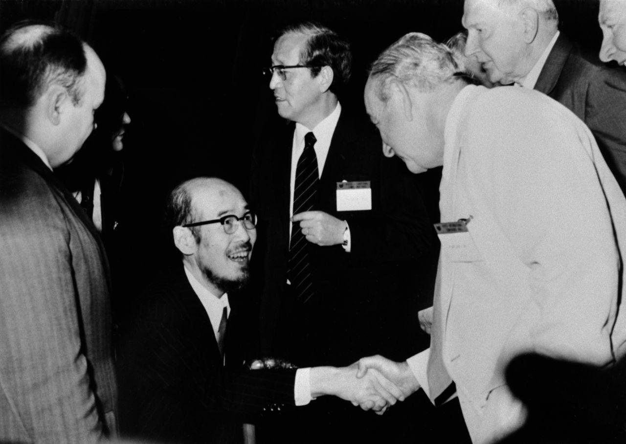 Юкава в инвалидной коляске приветствует иностранных учёных на Пагуошской конференции (1975), впервые проводившейся в Японии. (Международный конференц-центр Киото, © Jiji Press)