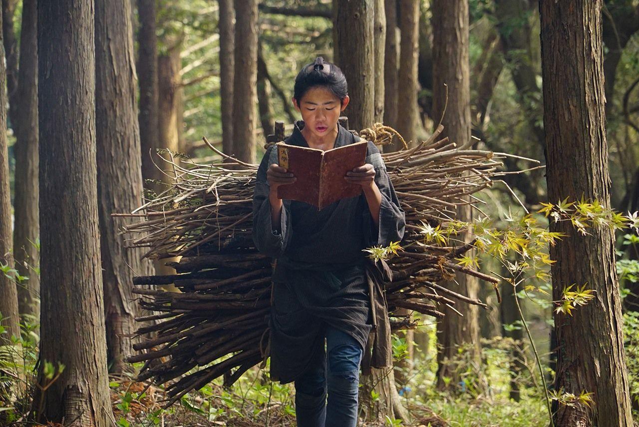 Молодой Ниномия (актёр Андо Микото) улучает моменты, чтобы учиться, пока несёт хворост, в фильме 2019 года «Ниномия Киндзиро» (© Производственный комитет фильма «Ниномия Киндзиро»)