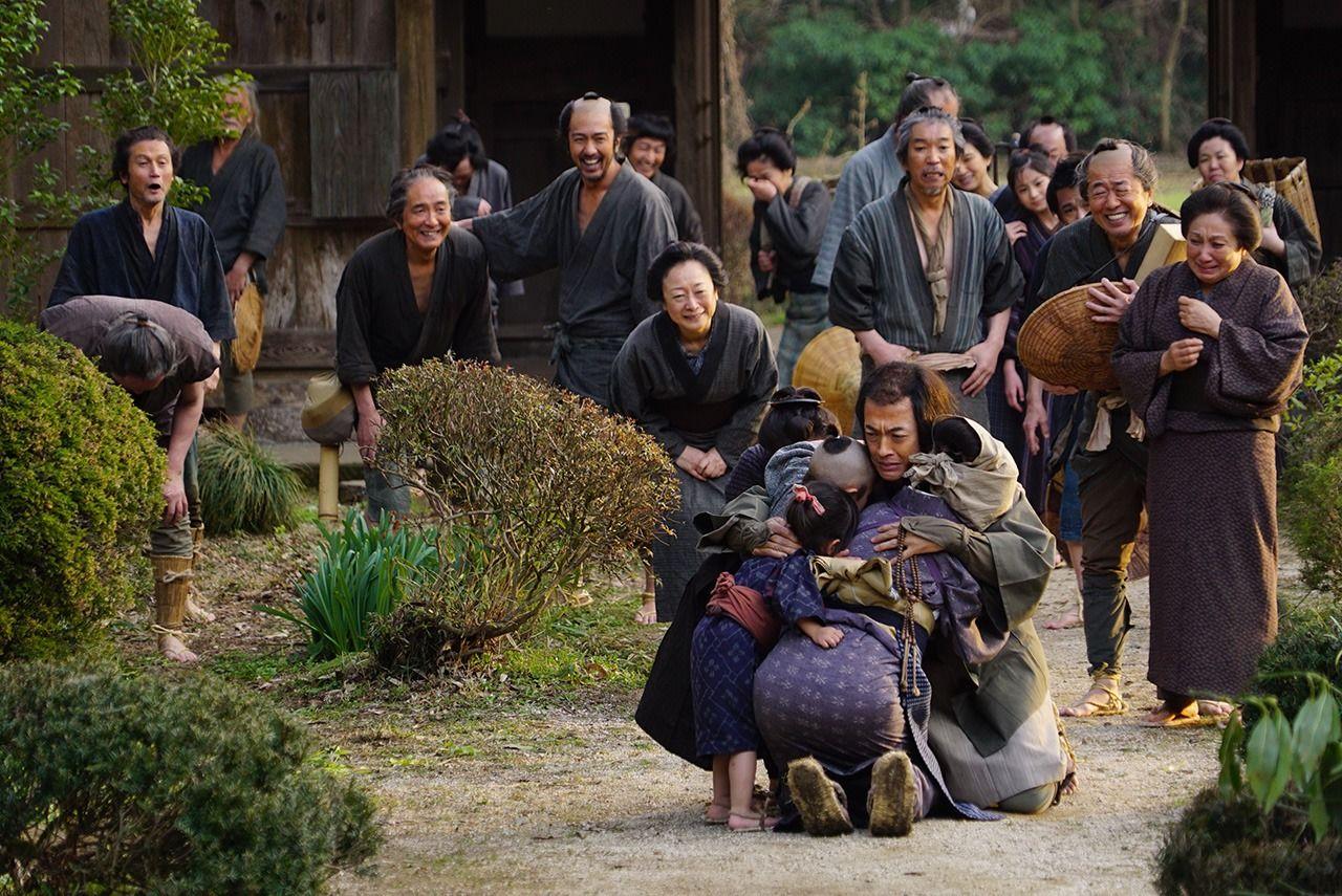Семья и друзья приветствуют Ниномию в Сакурамати после возвращения из храма (© Производственный комитет фильма «Ниномия Киндзиро»)