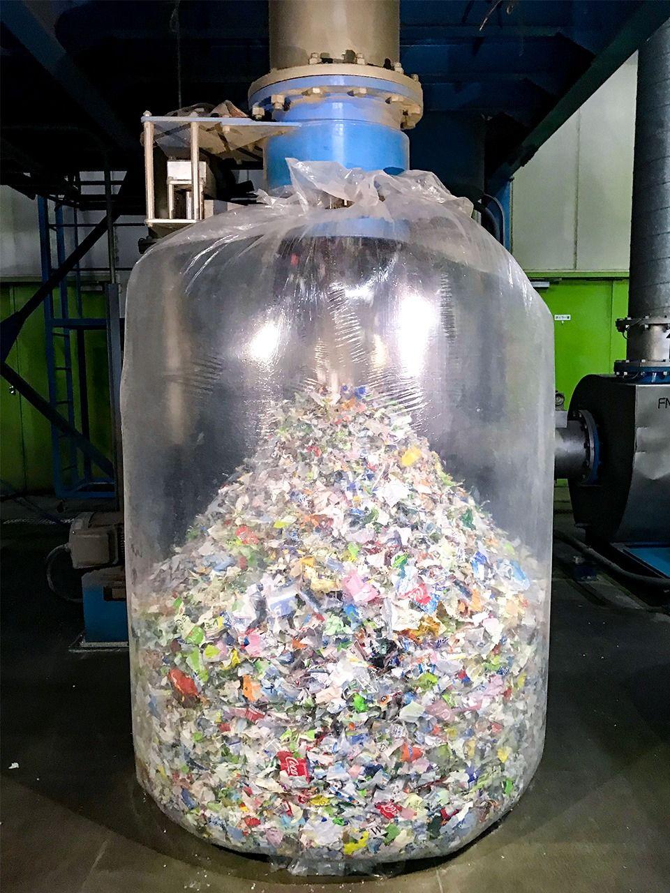 Гигантский пакет заполнен измельчёнными бутылочными этикетками. Струи сжатого воздуха помогают отделить фрагменты этикеток от ПЭТ-хлопьев
